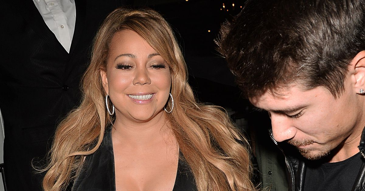 Mariah narrowly avoids nip slip in outrageous dress as toyboy helps her walk