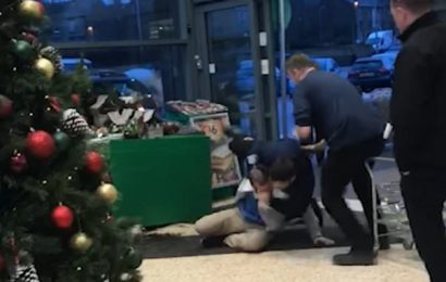 Security guard grapples with customer on the floor of supermarket