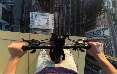 Maniac cyclist rides his mountain bike on the outside of a skyscraper