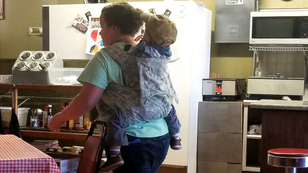 Waitress carries son on her back during shift because moms get it done