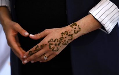 Meghan Markle shows off new henna tattoo to two little girls as she and Prince Harry visit boarding house in Morocco