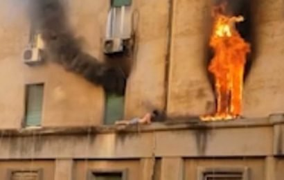 Man escapes blaze by clinging to narrow ledge by third-floor apartment