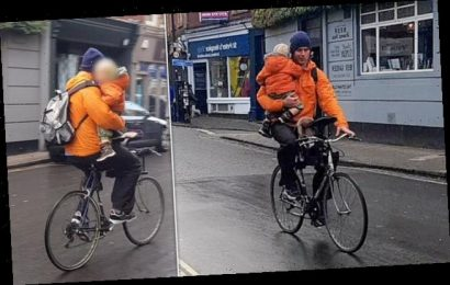 Cyclist is slammed for riding one-handed carrying a small child