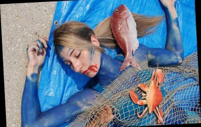Body-painted PETA activists protest seafood market as 'dead fish'