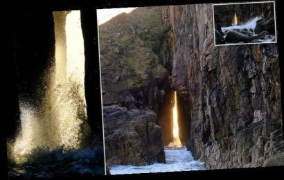 Light illuminates waves through a rock formation in Cornwall