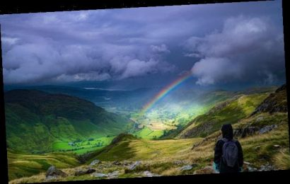 Girl watches rainbow form as storm clouds part over the Lake District