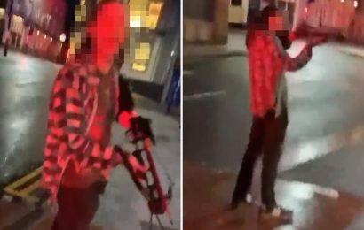 Shocking moment CROSSBOW-wielding thug points weapon at passer-by before being surrounded by cops